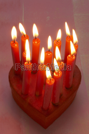 burning red candles on gift box