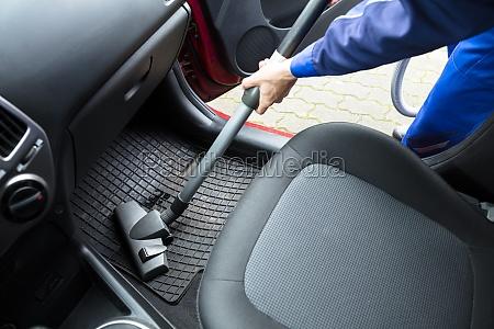 handymans hand vacuuming car mat