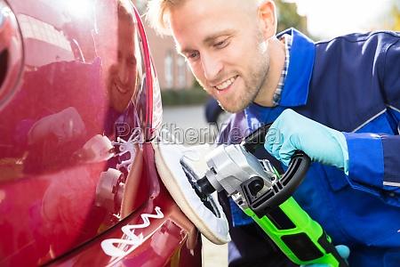male worker polishing car