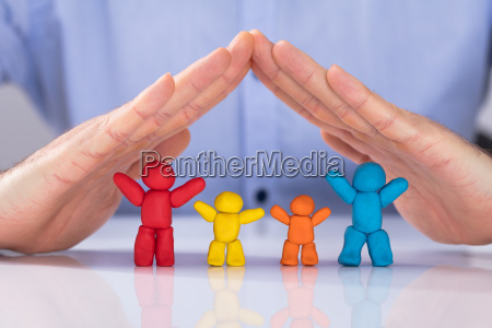 hand protecting the colorful family made