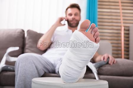 happy young man with broken leg