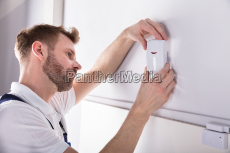 electrician installing security system door sensor
