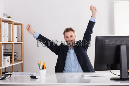 happy young businessman sitting in office