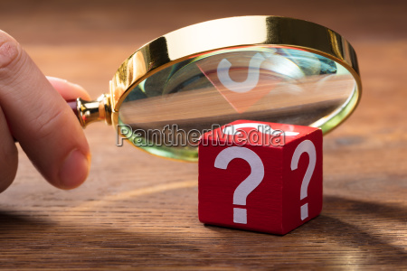person looking at wooden red block