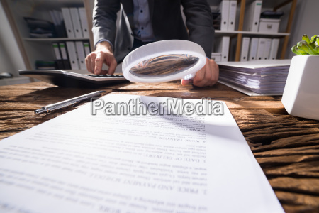 businessperson looking at document with magnifying