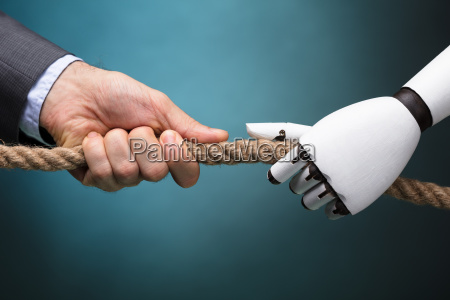businessperson and robot playing tug of