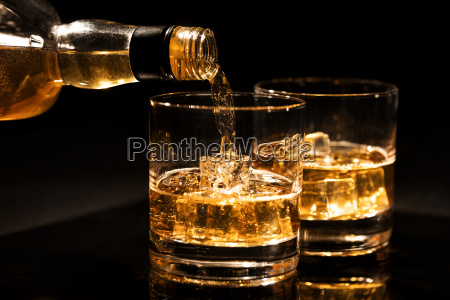 pouring whiskey into a glass from