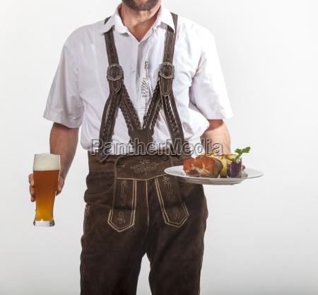 bavarian man in lederhosen serves roast