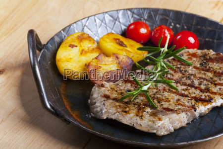 grilled steak with rosemary in a
