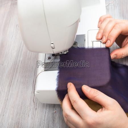 designer sews strips of fabrics for
