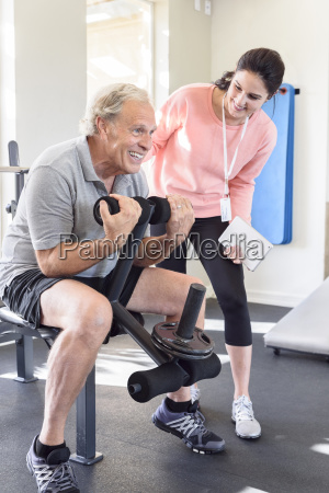 caucasian trainer watching man strengthen arms