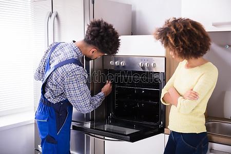 repairman fixing oven in kitchen