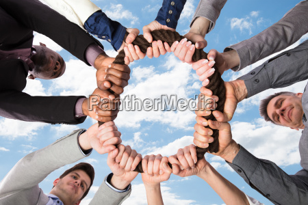 group of businesspeople holding rope together