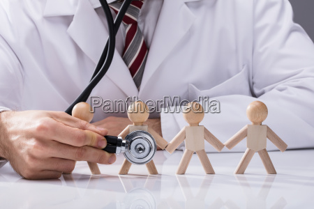 doctor examining wooden figures with stethoscope
