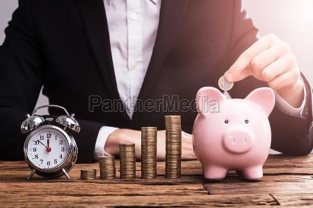 businesspersons hand putting coin in piggybank