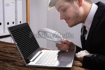 businessman looking at binary code with