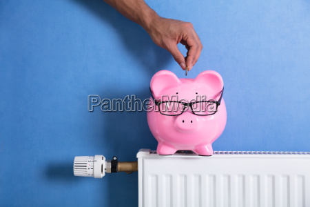 persons hand adjusting thermostat