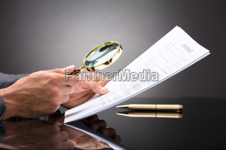 judge looking at document with magnifying