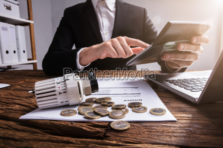 businesspersons hand calculating invoice with calculator
