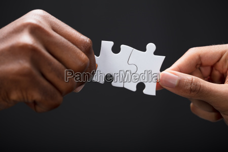 hands combining white puzzle pieces
