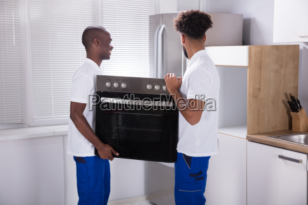 two male workers placing the oven