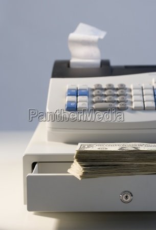 cash register with pile of cash