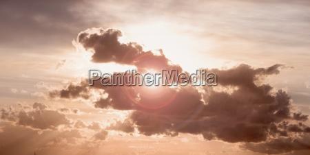 sun peeking through dark cloud