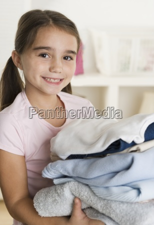 young girl holding laundry