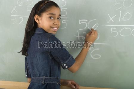 girl writing on chalkboard