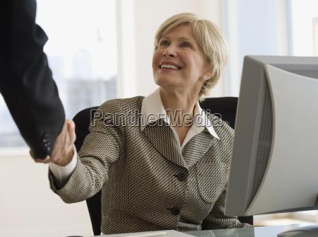 senior businesswoman shaking hands at desk