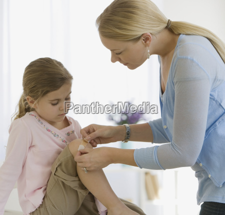 mother bandaging daughters knee