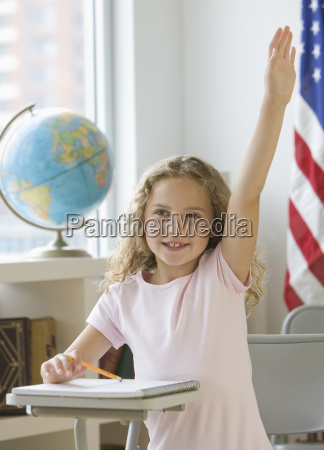 girl raising hand at school desk