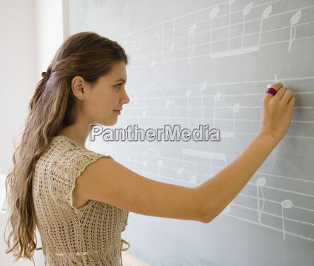 girl writing music on blackboard