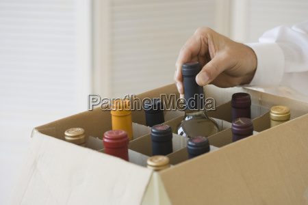 man taking wine bottle out of