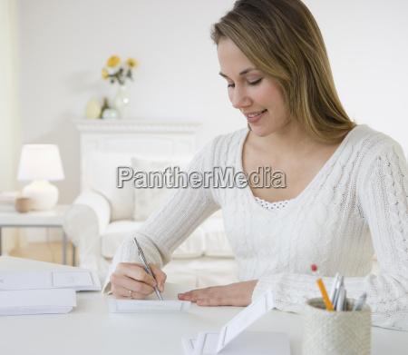 woman, writing, at, desk - 23891408