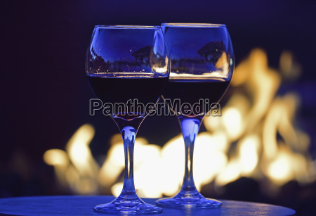 glasses of red wine against fire