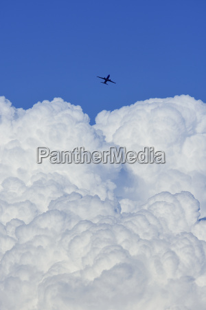 airplane flying over large cloud