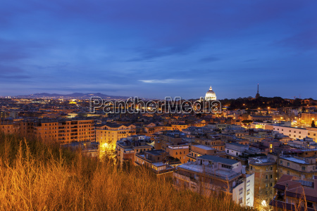 illuminated st peters basilica with townscape
