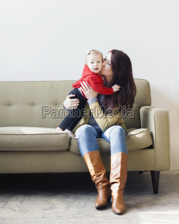 portrait of mother sitting on sofa
