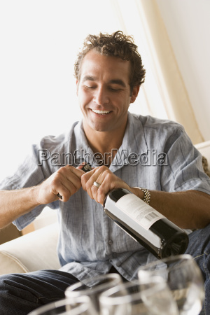 smiling man opening bottle of wine
