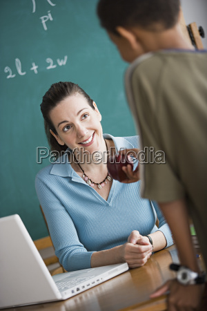 boy attempting to bribe teacher with