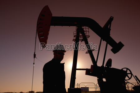 silhouette of oil worker by pump