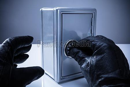 thiefs hand unlocking safe