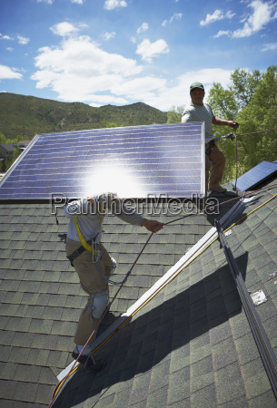 construction workers installing solar panels on