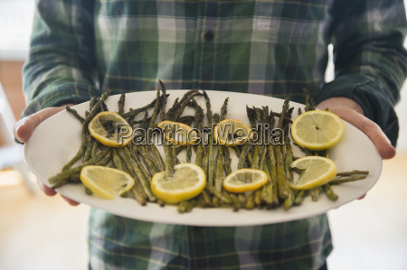 man holding platter with asparagus and