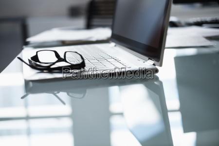 eyeglasses and laptop on desk in
