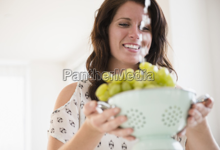 portrait of young woman washing grapes