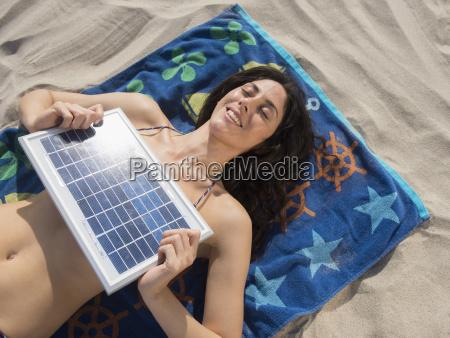 woman sunbathing with solar panel at