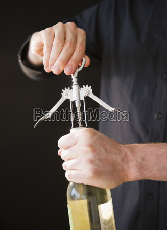 man opening wine bottle close up