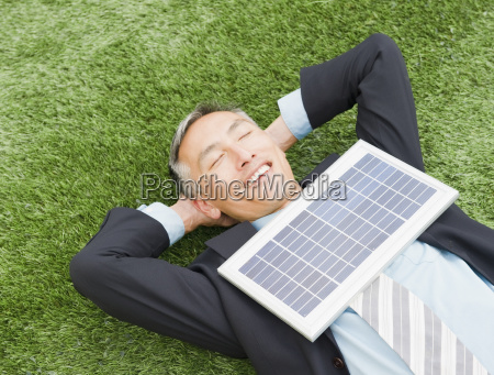 happy businessman lying on grass with
